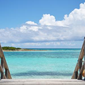 a wooden boat dock with an opening of a stairway to the beach and crystal clear blue waters great for snorkeling bonefish fishing scuba and spearfishing