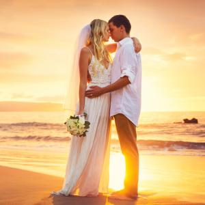A happy newly married couple poses for wedding photos in white wedding dress on pink white sand beach holding flowers with a backdrop of the beautiful caribbean ocean and golden rays of the setting sun