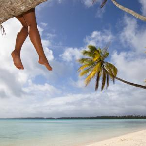 girl sitting on palm tree relaxing with feet dangling in the bahamas andros island harbour island treasure cay spanish cay cat cay green turtle cay