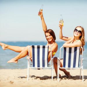two girls on beach in bahamas kicking back relaxing drinking beer and celebrating
