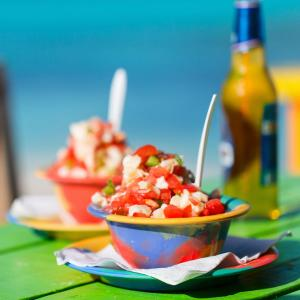 Crab and shrimp ceviche sits in a colorful bowl on a bright green wooden table with a beer in the background, an authentic plate in the Bahamas