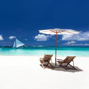 Two beach chairs and white umbrella sit on a white sand beach with a perfect view of a sailboat cruising along calm blue clear caribbean ocean waters