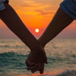 A couple holds hands with the sunset directly visible in between their wrists giving off a perfect view of the pink sunset over the rugged waves