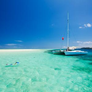 a catamaran is docked mooring near a sandbar with snorkelers and scuba divers explore the ocean floors and reefs for colorful fish and sea life in the bahamas cuba or turks and caicos