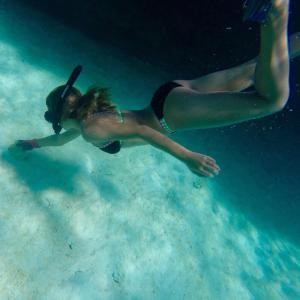 girl scuba diving snorkeling to catch conch bahamas caribbean ocean eleuthera